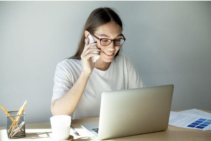 Chica joven llamando por teléfono mientras tiene el ordenador abierto y está sentada en su escritorio