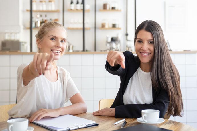 Dos chicas señalando con el dedo índice mientras toman un café sentadas en una cafetería