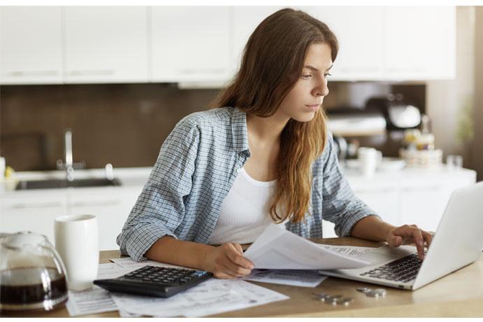 Mujer mirando el portátil y con papeles en la mano y encima de la mesa junto a una calculadora