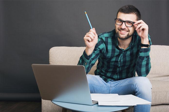 Chico joven con gafas y camisa a cuadros levantando la mano con un lápiz mientras en la mesa pequeña hay un ordenador abierto y papeles por encima