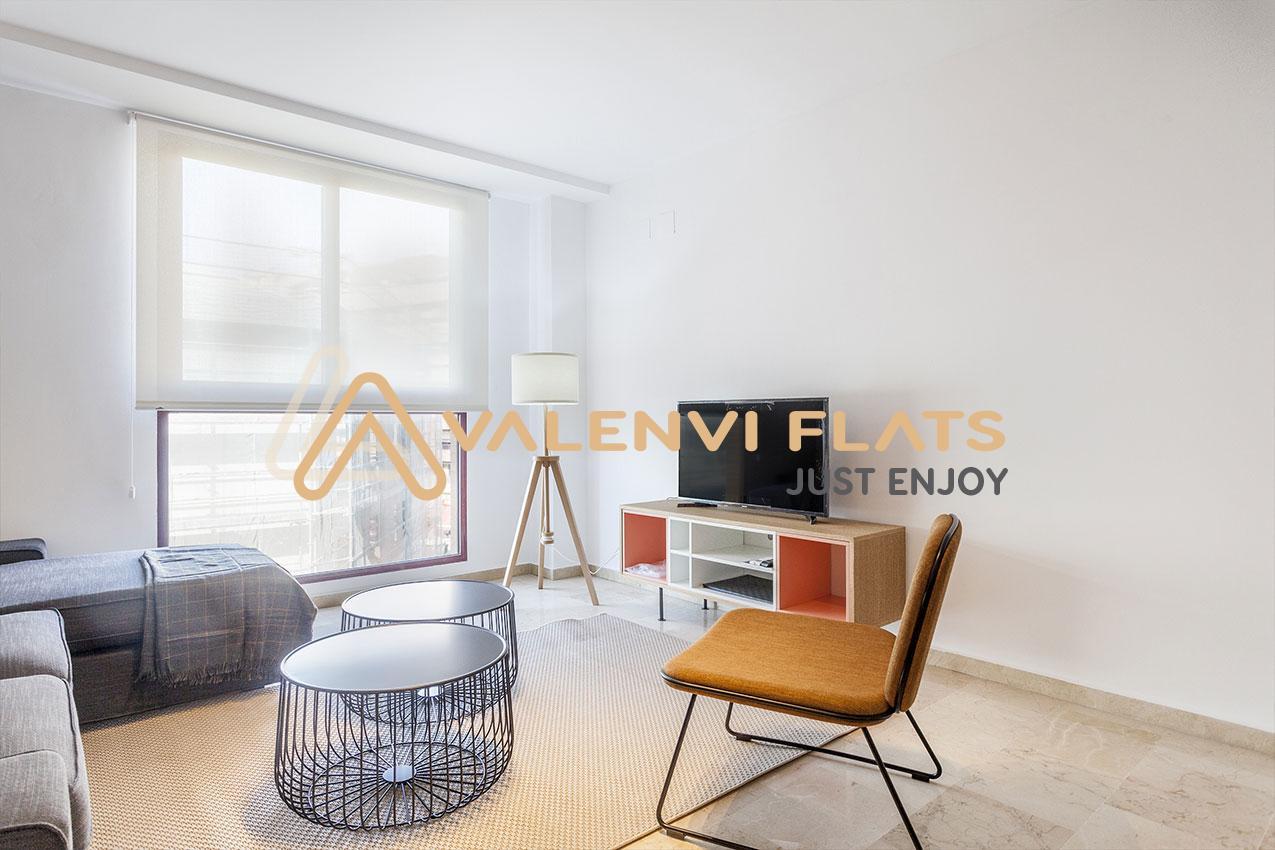 Salón con silla, mesas negras, lámpara mesa con televisión y al fondo ventanal con estor blanco