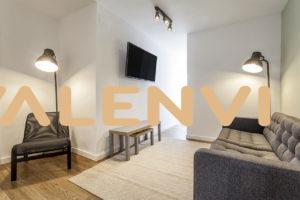Hall con silla y lámpara, mesita pequeña, televisión colgada de la pared y a la derecha, sofá dos plazas con una segunda lámpara de pie