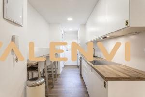 Plano horizontal de la cocina con taburetes y barra americana a un lado y al otro, encimera con vitro y armarios despensa