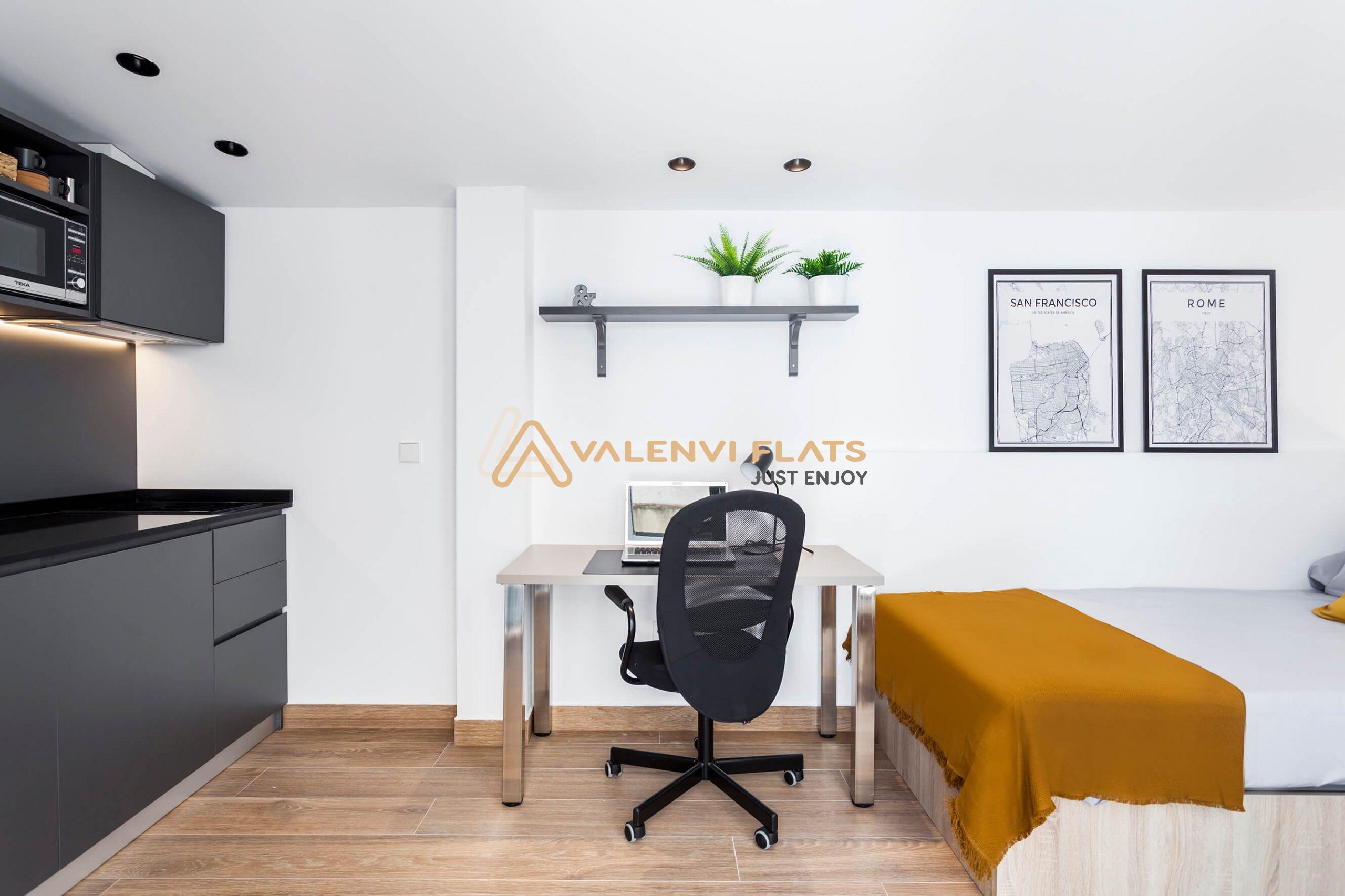Panorámica del estudio individual con cocina office a un lado y su microondas, al centro la mesa de estudio y las baldas, y al lado derecho, la cama y unos cuadros