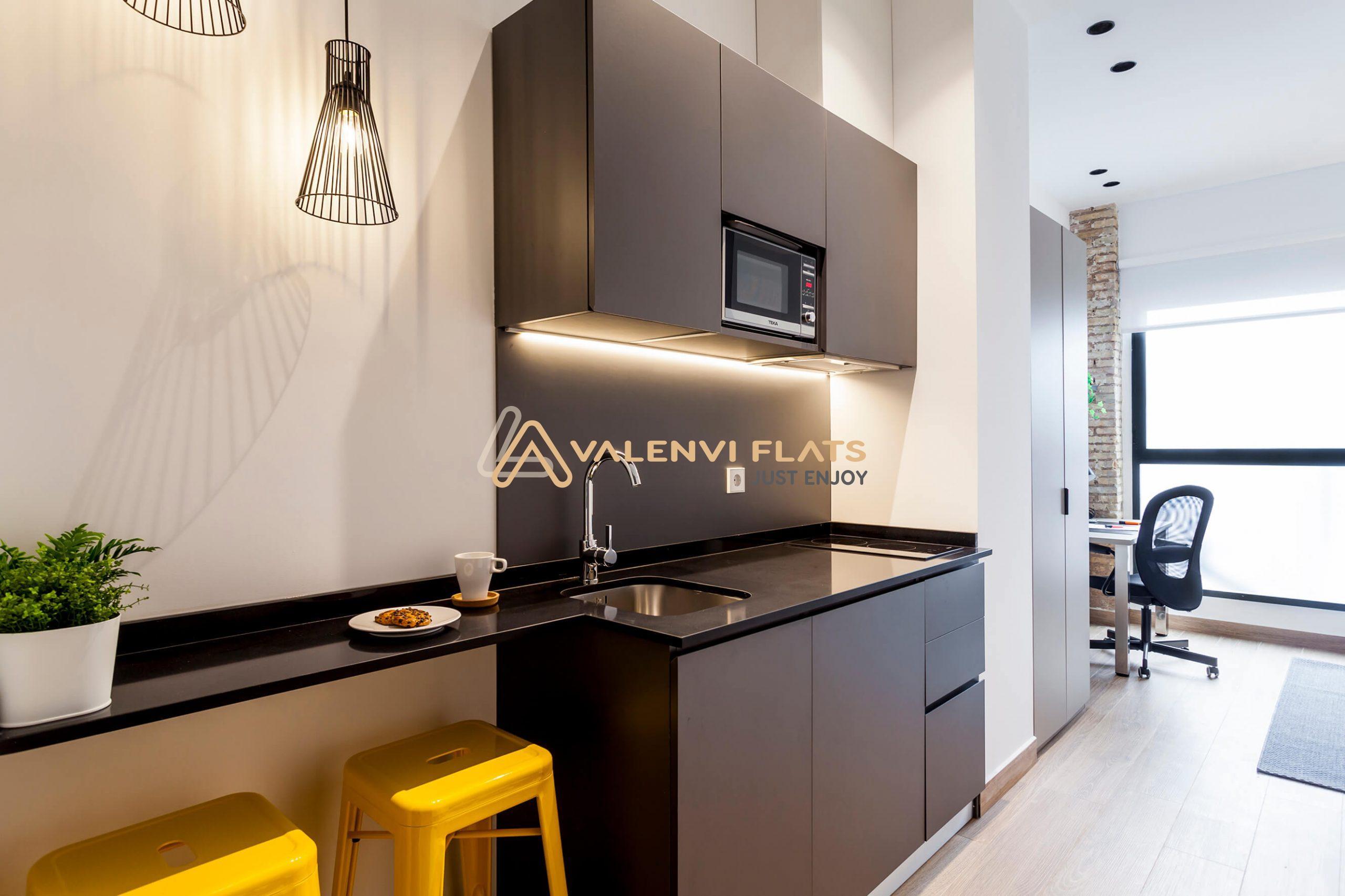 Primer plano de la cocina office equipada con electrodomésticos con los taburetes y la barra americana y al fondo el escritorio y la silla