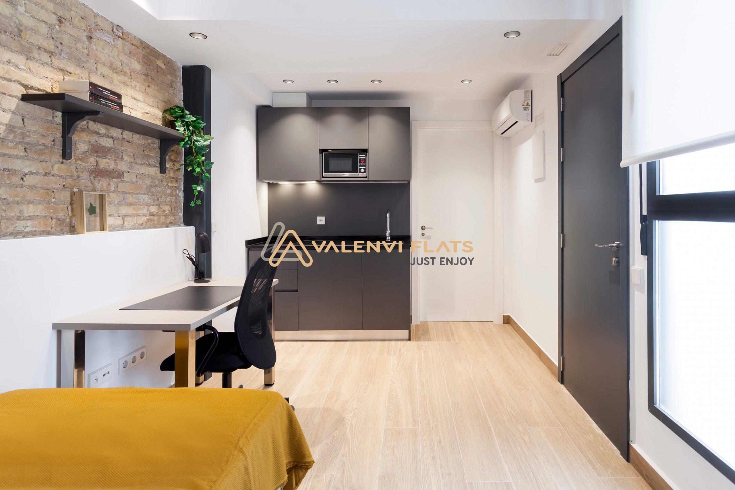 Imagen de la amplitud del estudio con el escritorio, la cocina oficce, las baldas, el aire acondicionado, el baño privado y la entrada al estudio