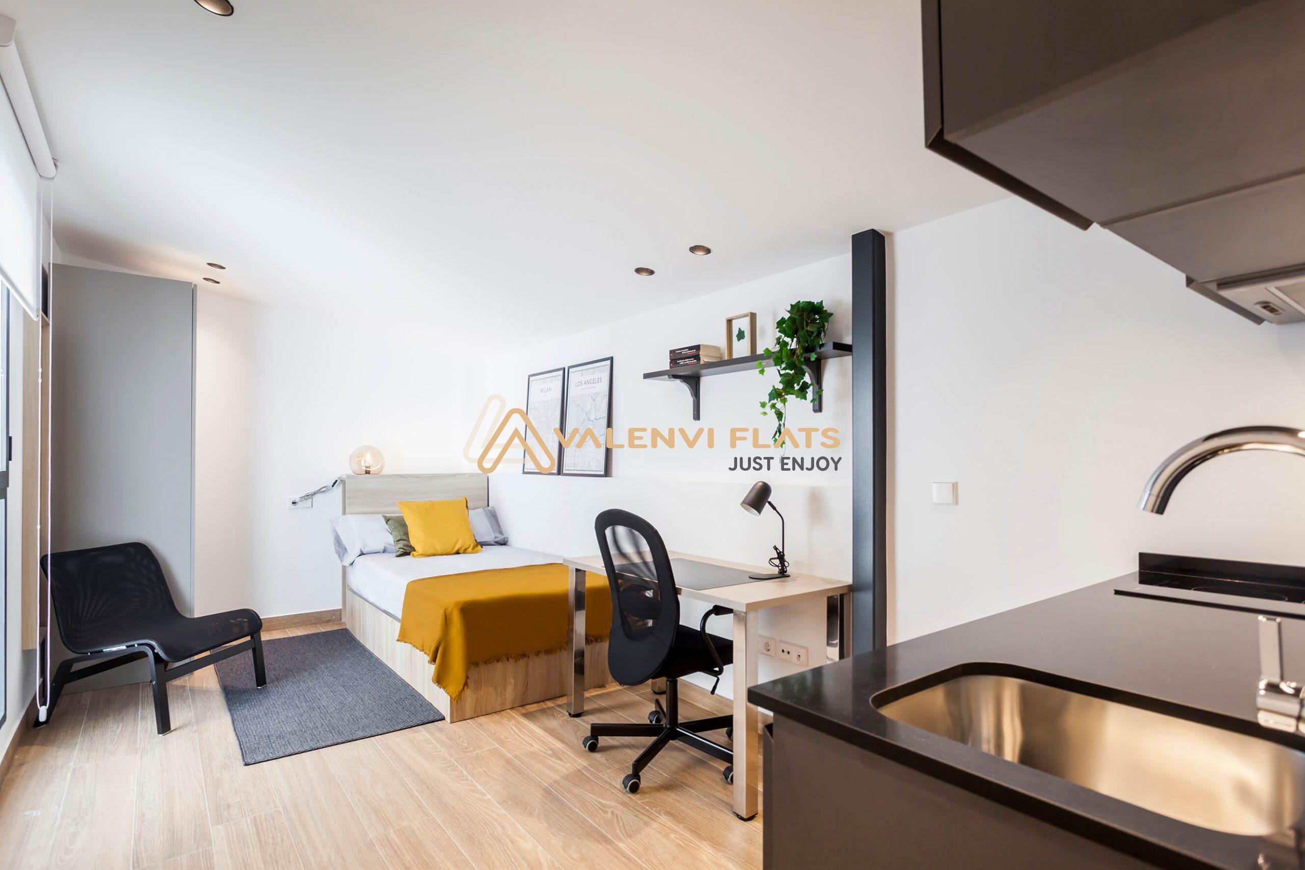 Vista abierta de todo el estudio de cama individual, con armario al fondo y sillón, decoración y escritorio y por último encimera de la cocina office