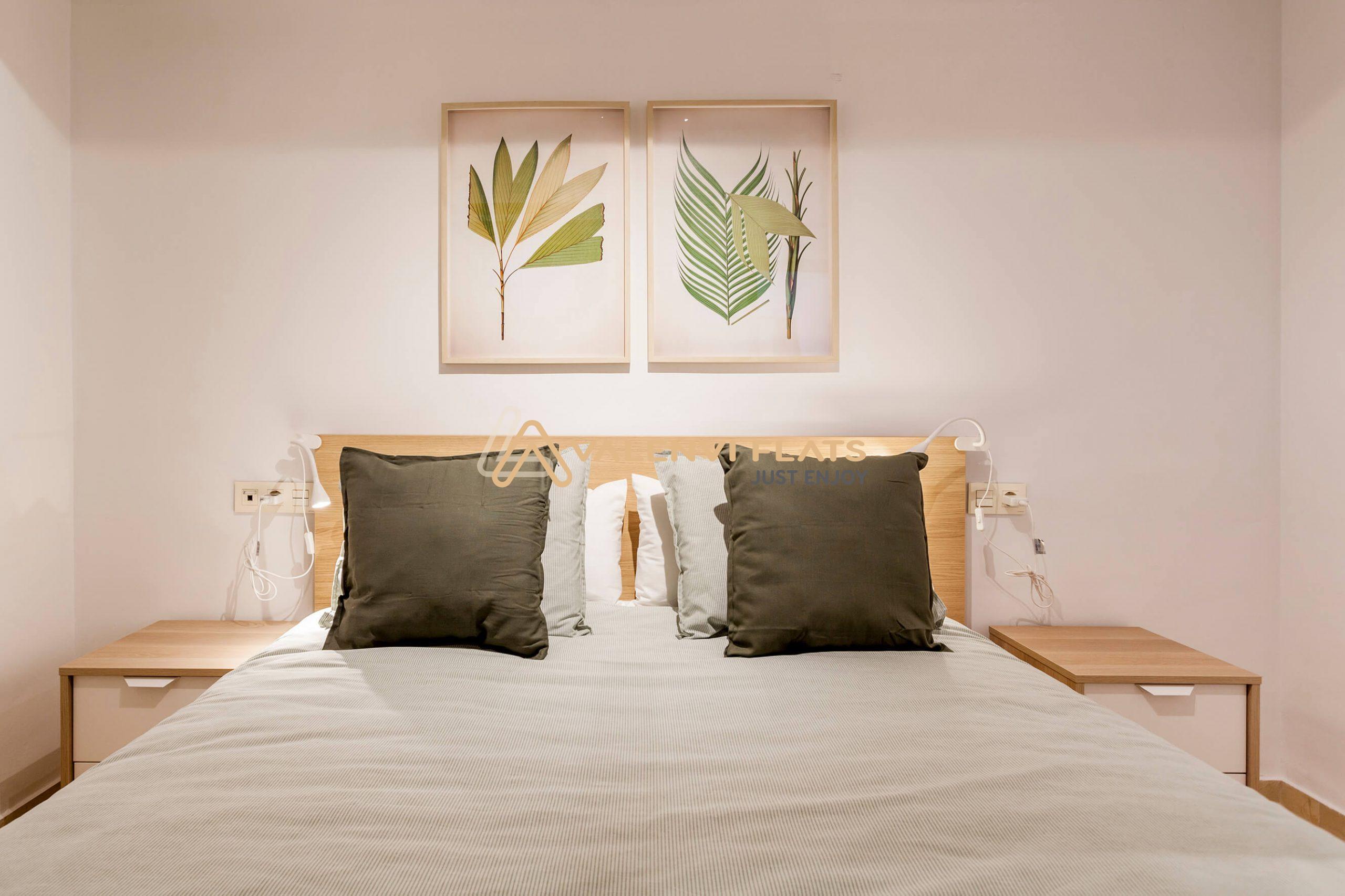 cama con dos cojones verdes y dos cuadros con símbolos naturales