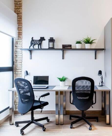 Dos sillas y dos escritorios con portátil y plantas alrededor