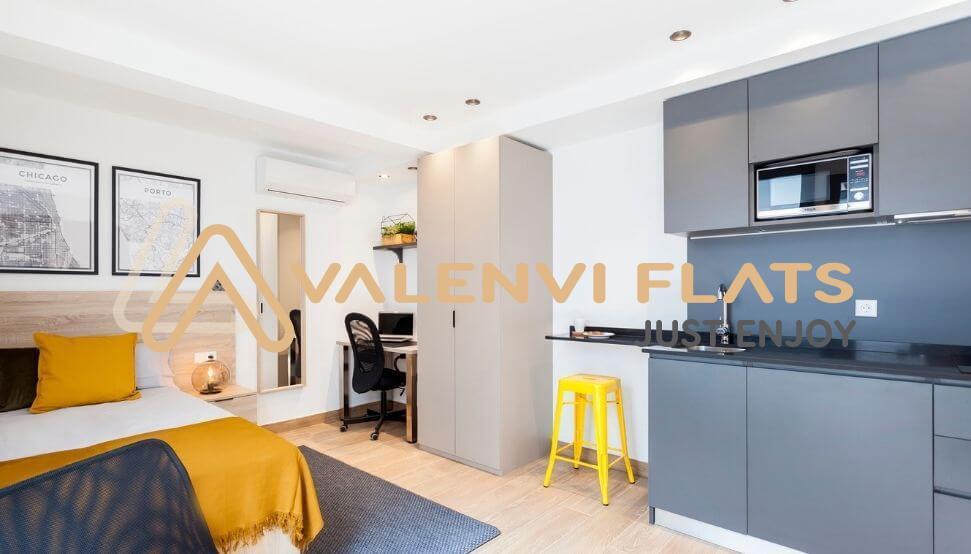 Habitación con una cama, silla, escritorio, armario y cocina office con barra americana y taburete amarillo