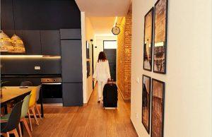 Mujer vestida de blanco con maleta dirigiéndose hacia la puerta del alojamiento