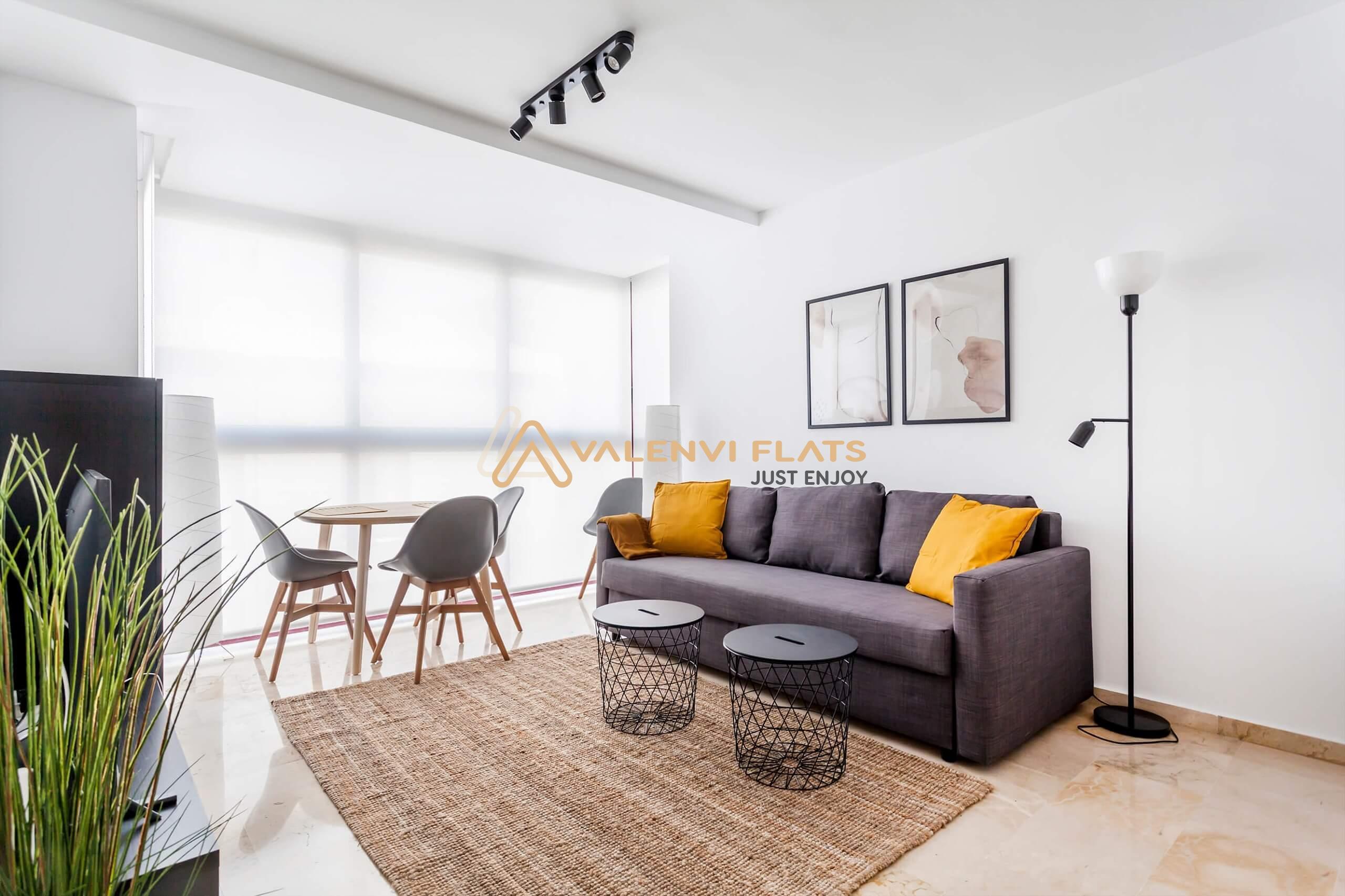 Sofá al fondo de la imagen junto a una mesa con sillas y en primer plano una planta