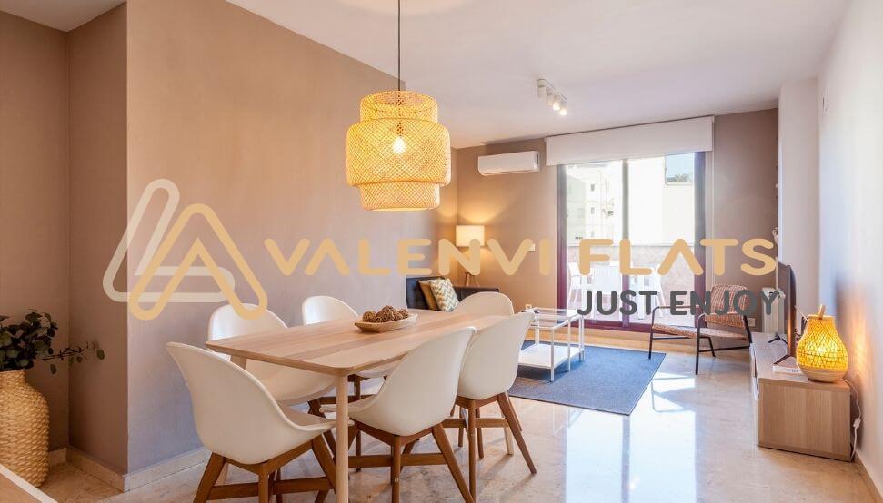 Salón con mesa y sillas, lámpara, sofá y televisión y de fondo, terraza soleada con sillas