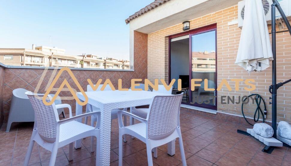 Terraza con mesas y sillas blancas, la entrada al salón y de fondo vistas con fincas